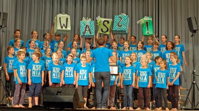 Kinder stehen auf Bühne und singen im Chor, alle im selben T-Shirt