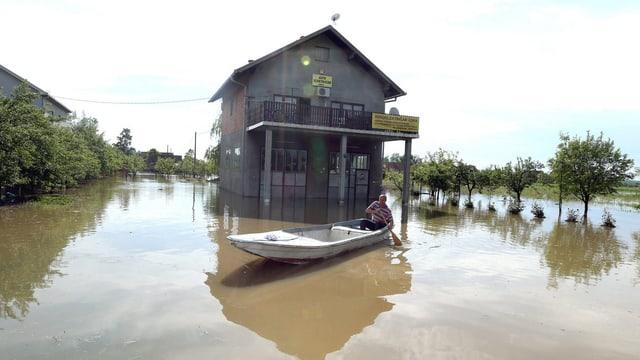 Haus, völlig vom Wasser eingeschlossen. Davor ein Mann in einem Boot.