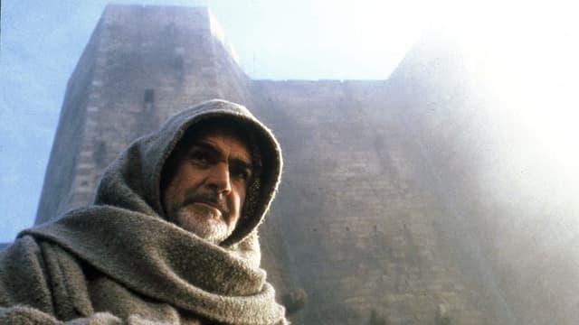 Ein Mann mit einer grauen Kapuze steht vor einem mächtigen, burgartigen Gebäude.