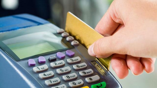 Eine Person zieht eine Kreditkarte durch ein Lesegerät