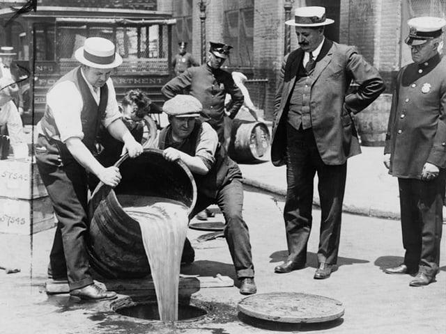 Schwarzewissbild: Männer kippen den Inhalt eines grossen Fasses in einen Abfluss.