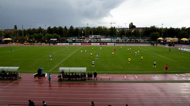 Blick auf ein Fussballfeld mit Tartanbahn auf der Seite. Verschiedene Fussballspieler stehen auf dem Feld