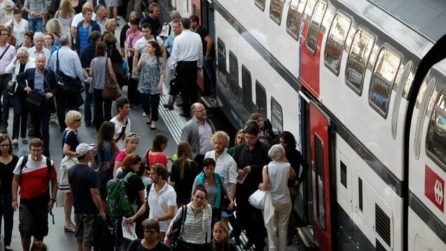 Persunas che entran en il tren.