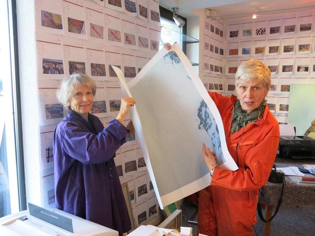 Maja Wagner und Verena Welten lassen einen grossflächigen Fotodruck durch den Schredder.