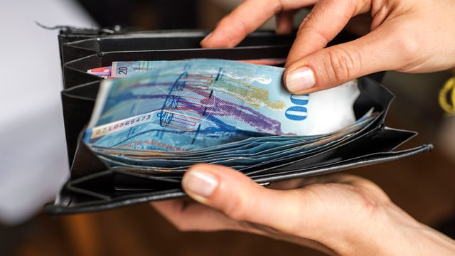 Jemand nimmt eine Hunderternote aus einem Portemonnaie.