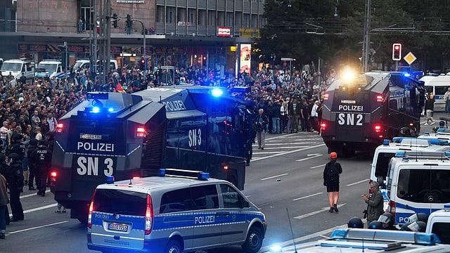 Polizeiautos vor Demonstranten