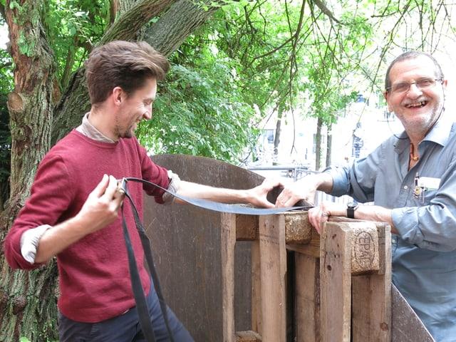 Künstler befestigen ein Holzpalett an einem Metallvordach.