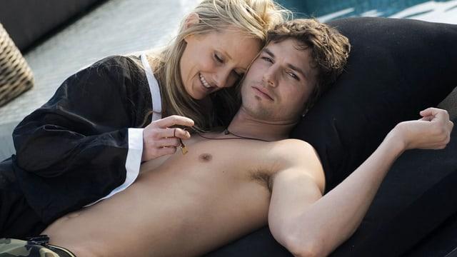 Ein Mann mit nacktem Oberkörper liegt auf einem Divan. Eine blonde Frau neigt sich über ihn.