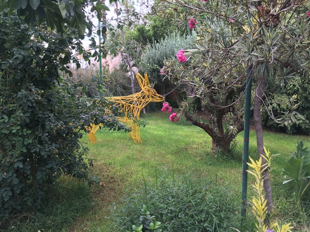 Ein aus Metallstangen geformter, gelber Vierbeiner steht in einem Garten.