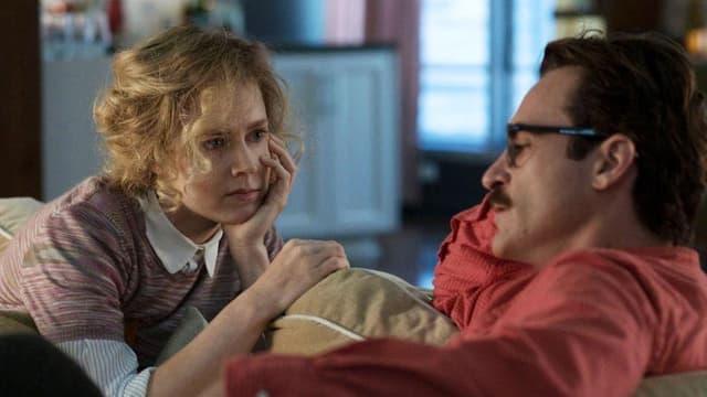 Eine Frau und ein Mann sitzen auf einem Sofa und sprechen zusammen.