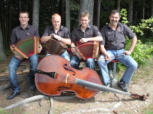 Die vier Musiker sitzen am Waldrand auf einer Bank. Vor ihnen liegt ein Kontrabass am Boden. Drei der Musiker halten ein Schwyzerörgeli auf den Knien.