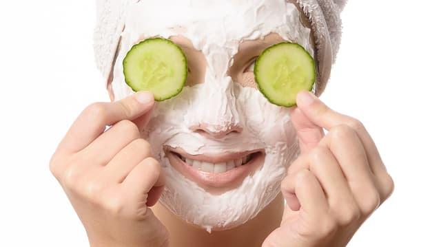 Eine Frau mit einer Gesichtsmaske hält sich Gurken über die Augen.