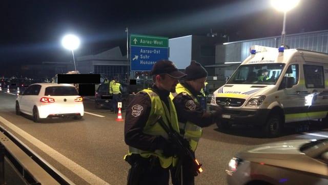 Zwei Polizisten stehen auf einer Strasse und kontrollieren Fahrzeuge