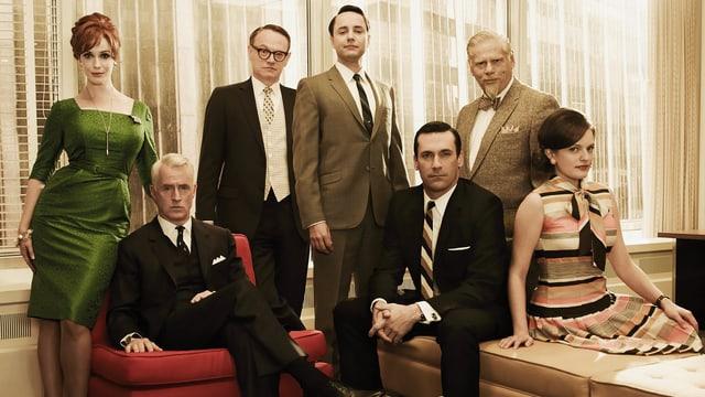 Zwei Frauen und fünf Männer in eleganter Kleidung.