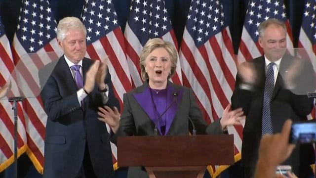 Hillary Clinton am Rednerpult, daneben Bill Clinton und Tim Kaine.