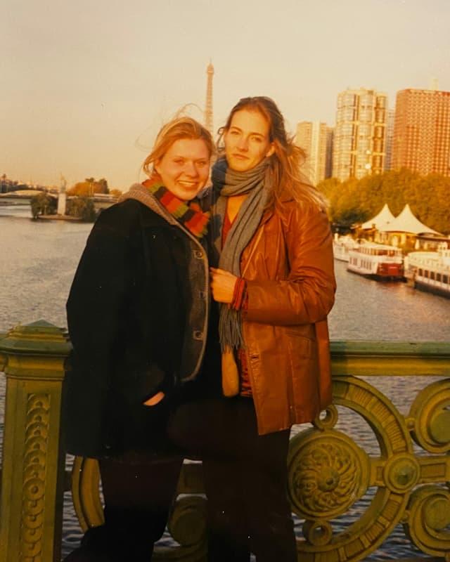 Zwei junge Frauen posieren auf einer Brücke in Paris.