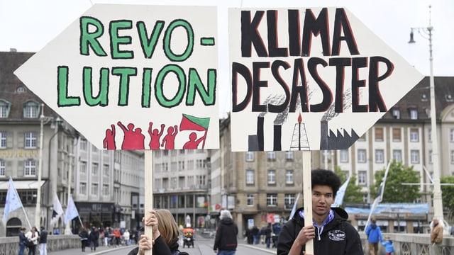 Demonstranten halten Schilder mit der Aufschrift «Revolution» und «Desaster».