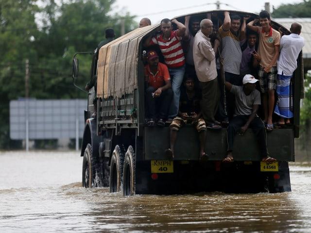 Menschen werden in einem Lastwagen durch eine überflutete Strasse abtransportiert.