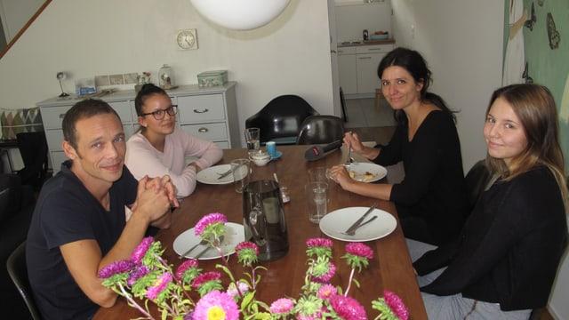 Eine vierköpfige Familie mit dunklem Haar am gedeckten Esstisch
