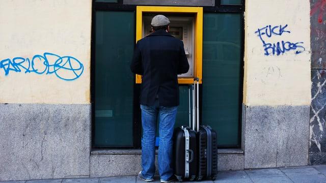 Ein Mann mit einem Rollkoffer steht vor einem Bankomaten. Linsk und rechts Graffitti an der Wand.
