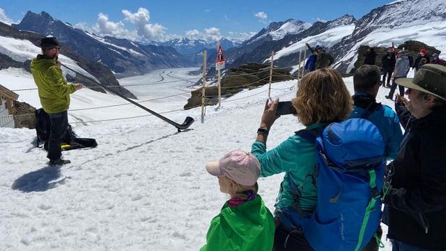 Alphornbläser vor dem Rhonegletscher, Leute hören zu und machen Fotos.