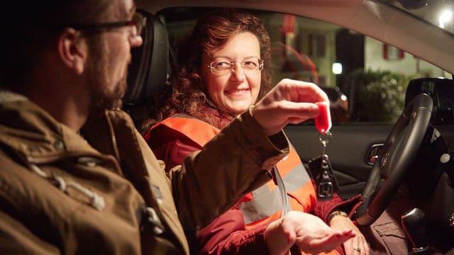 Mann händigt freiwilliger Chauffeurin Autoschlüssel aus