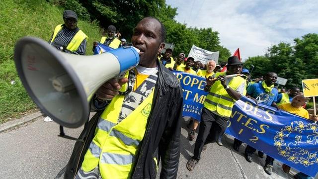 Protestumzug. Im Vordergrund Mann mit Megafon, dahinter Menschen mit Transparent