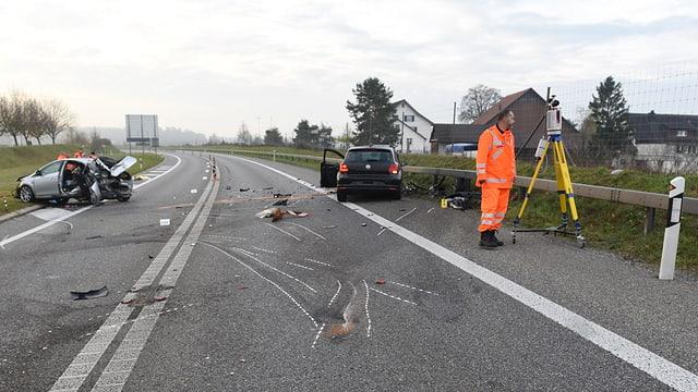 Polizeibeamte arbeiten auf einer Unfallstelle, im Hintergrund zwei stark beschädigte Autos