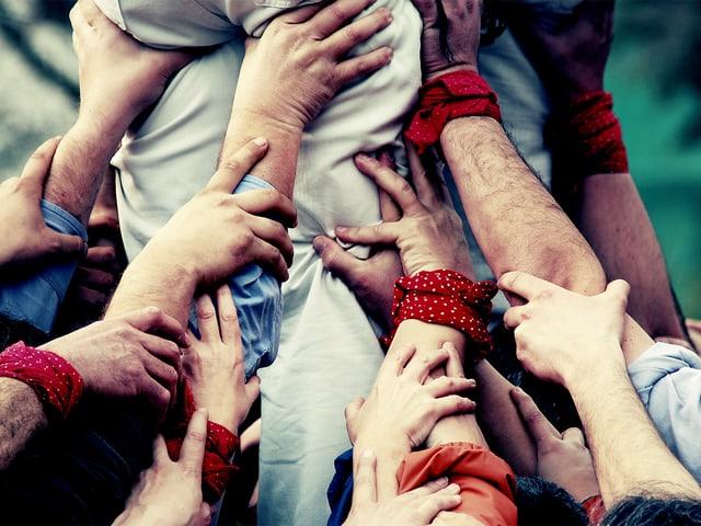 Viele Hände greifen zusammen und stützen eine Person.