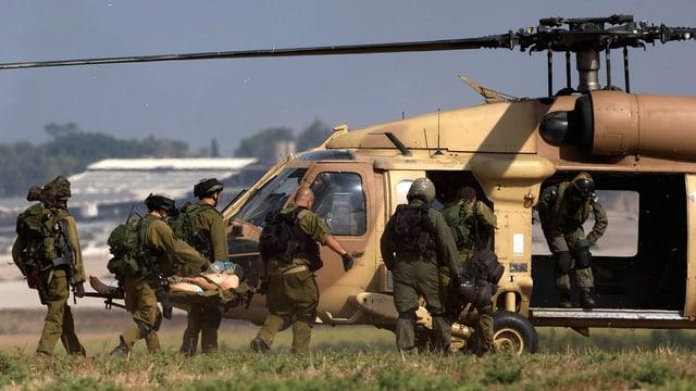 Soldaten transportieren einen Verletzten Kollegen in einem Hubscharauber