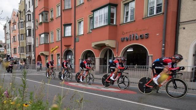 Fünf Velofahrer in rot-schwarzen Trikots fahren durch Innsbruck.