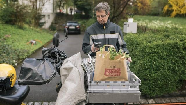 Eine Pöstlerin trägt Briefe und Gemüse aus.