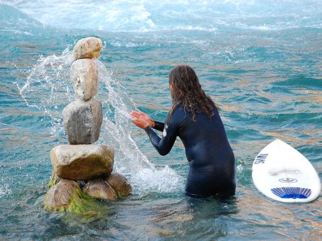 Mann im Neopren-Anzug bespritzt ein Steinmannli im Wasser