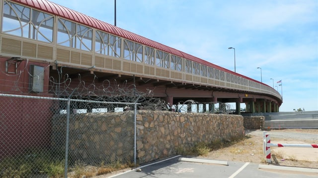 Brücke über eine Grenze und Stahlzaun.