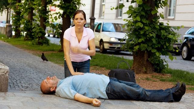 Eine Frau kniet vor einem Mann, der bewusstlos am Boden liegt.
