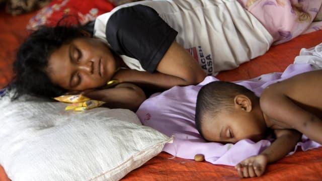 Eine Rohingya-Frau liegt schlafend neben ihrem Kind.