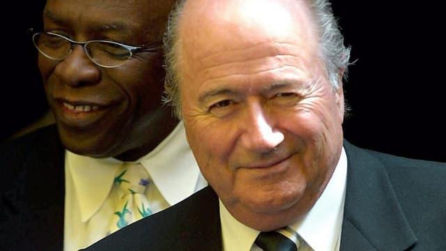 Warner steht hinter Blatter, beide lächelnd und im Anzug.