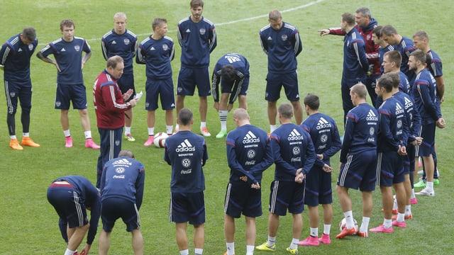 Trainer Leonid Sluzkij gibt bei einer Trainingseinheit der versammelten Mannschaft Anweisungen.