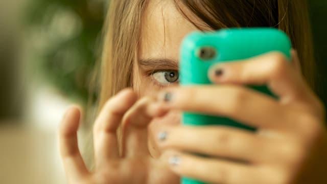 Ein Mädchen spielt mit seinem Handy.