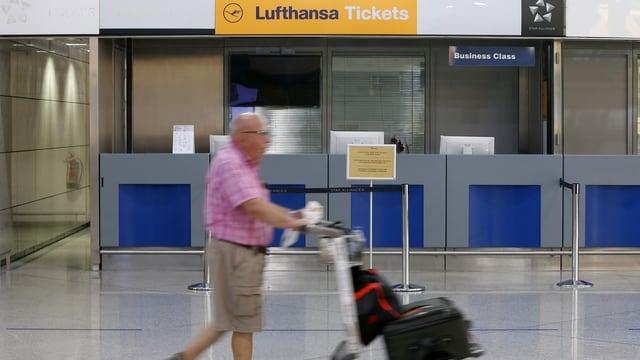 Ein Reisender mit Trolley geht an einem unbedienten Schalter der Lufthansa vorbei.