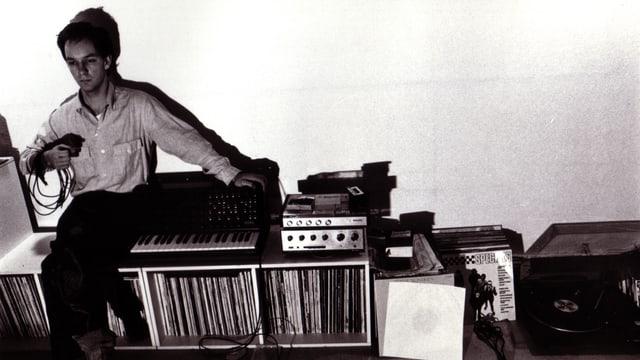 Schwarzweissfoto: Ein junger Mann sitzt auf einem Plattenregal neben einem Synthesizer.