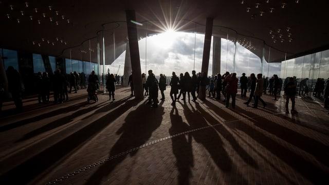 Silhouetten von Menschen vor einem Sonnenuntergang.