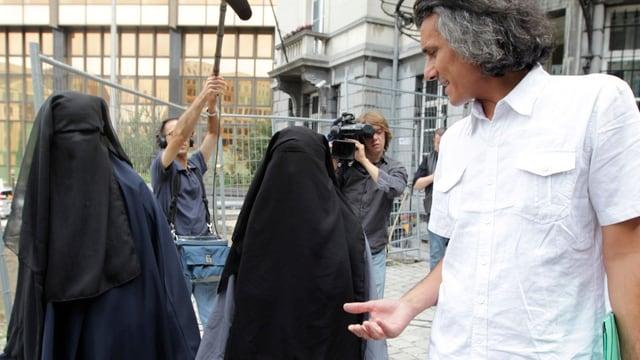 Rachid Nekkaz spricht zu zwei verschleierten Frauen.
