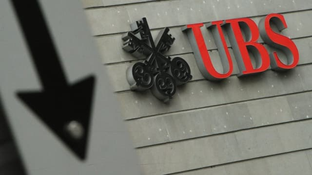 Ein Logo der UBS, daneben ein Pfeil in Abwärtsrichtung