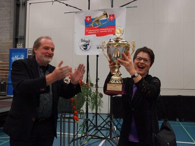 Die Dirigentin stemmt den Pokal in die Höhe.
