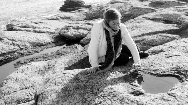 Eine Frau sitzt am Meer auf einem flachen Felsen, durch den Stein haben sich kleine Bäche gefressen. Die Frau sitzt vor einer Wasserpfütze und lächelt. Sie trägt die Haare locker zusammengebunden, einen Schal und eine Strickjacke.