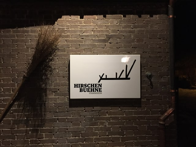 Eine Backsteinwand mit einem weissen Schild, mit schwarzer Schrift das Logo der Hirschenbühne.