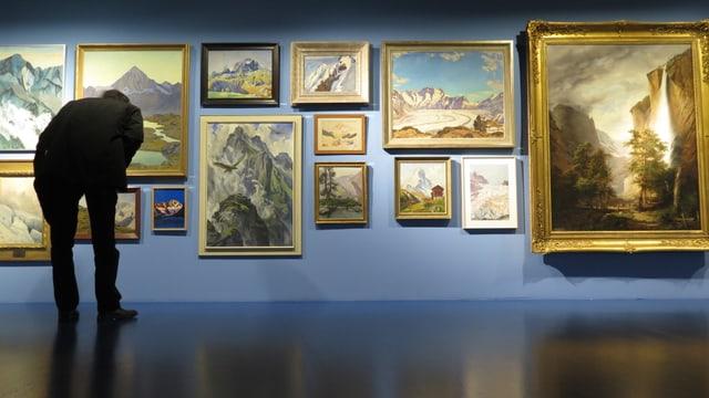 Mann steht vor einer Wand in der Ausstellung