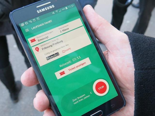 Smartphone mit App «Fairtiq» in der Hand eines Fahrgastes.