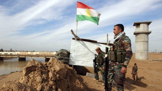Kurdische Kämpfer stehen neben einer kurdischen Fhne